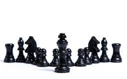 Chess pieces. Black chess pieces lined up in front of white background - Concept of leadership Stock Photos