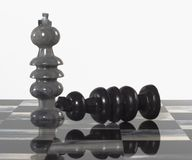 Chess Pieces - Black Resigns to White. Onyx stone hand-carved chess set board and pieces Stock Images