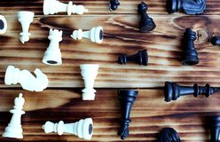 Chess pieces black and white scattered on the table royalty free stock photography