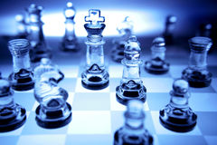 Chess pieces in blue tone. Partial view of a chess board with glass pieces in blue tone royalty free stock photo