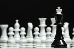 Chess pieces. On the board on a dark background Royalty Free Stock Image