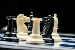 Chess pieces on the board. White and black chess pieces during the fight royalty free stock photography