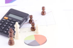 CHESS PIECES WITH A CALCULATOR AND PAPER Royalty Free Stock Photo