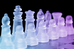 Chess Pieces. On check board with selective focus on king Royalty Free Stock Photos