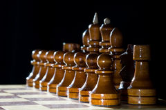 Chess pieces on chess board. Brown chess wooden pieces on chess board with dark background royalty free stock photo