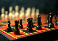 Chess pieces on a chessboard. Black and white chess pieces on a chessboard Stock Images