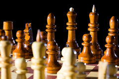 Chess pieces on chessboard. Black and white chess pieces on chessboard with black background royalty free stock photo