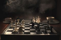 Chess pieces on the chessboard. Dark background and smoke stock photo