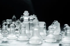 Chess pieces. Close up of a transparent chessboard with selective focus on the king blur effect Royalty Free Stock Photos