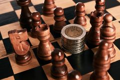 Chess pieces with coins stack on the chessboard Royalty Free Stock Photo