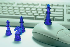 Chess Pieces and Computer. In Green Cast Royalty Free Stock Photography