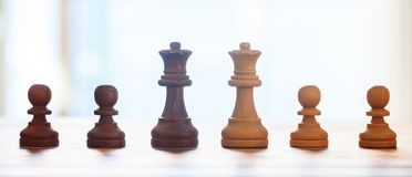 Chess pieces dark, light brown color. Closeup view of queens and pawns with details. Blur backdrop. Royalty Free Stock Photos