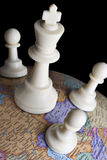 Chess pieces on an earth globe Stock Image