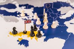 Chess pieces over an european map. Brexit concept. Chess pieces and flags on an European map focused in the black UK king and islands. Brexit negociations and royalty free stock photography