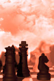 Chess pieces isolated against red sky Stock Images