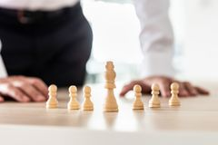 Chess pieces of king and pawns placed on office desk stock image