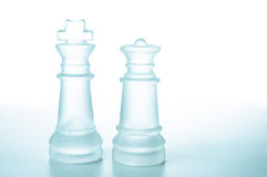 Chess pieces King and Queen. Glass chess pieces King and Queen are on a white background isolated royalty free stock photography