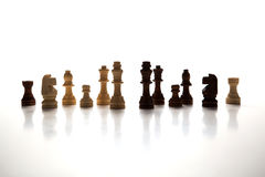 Chess pieces lined up in a row on a gray Royalty Free Stock Photos