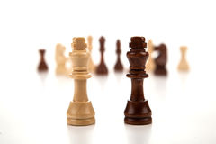 Chess pieces lined up in a row on a gray Royalty Free Stock Images
