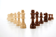 Chess pieces lined up in a row on a gray Stock Images