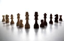 Chess pieces lined up in a row on a gray Stock Photography
