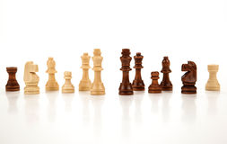 Chess pieces lined up in a row on a gray Royalty Free Stock Photography