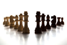 Chess pieces lined up in a row on a gray Stock Photos