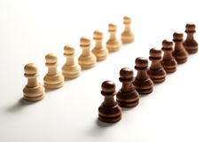 Chess pieces lined up in a row on a white Stock Image