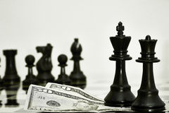 Chess pieces with money Stock Photography