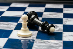 Chess pieces on the open field. White pawn won black queen on chessboard stock photos