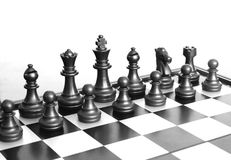 Chess pieces over its board with some illumination. Particular image about the black pieces of the chess game over its board illuminated by a white background Royalty Free Stock Image