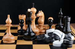 The chess pieces and pile of checkers placed on the chessboard. Royalty Free Stock Photo