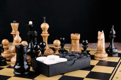 The chess pieces and set of checkers placed on the chessboard. Stock Photography