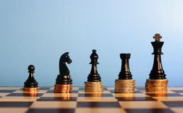 Chess pieces on stacked coins, Stock Image