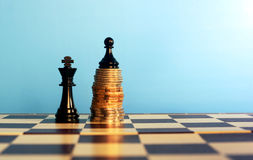Chess pieces on stacked coins Stock Photo