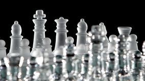 Chess pieces is standing on glass  board. Close up stock video footage