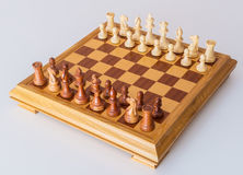 Chess pieces in starting position on a wooden Board Royalty Free Stock Image