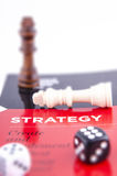 CHESS PIECES ON A STRATEGY BOOK WITH DICE Stock Photos