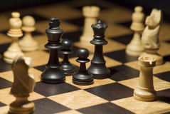 Chess pieces surrounded by opposition Stock Image