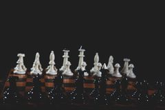 Chess pieces on the table. On black background stock image