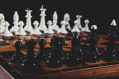 Chess pieces on the table. On black background stock photo