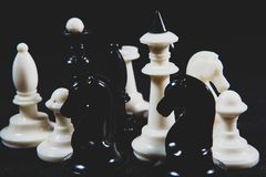 Chess pieces on the table. On black background royalty free stock image