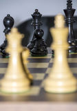Chess pieces. In vertical, white in the foreground are blurred Royalty Free Stock Image
