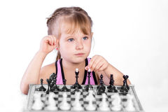 Chess player. Intelligent girl playing chess with the black pieces, looking away Royalty Free Stock Photo