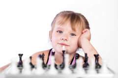 Chess player. Intelligent girl playing chess with the black pieces, looking away Royalty Free Stock Image