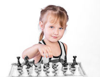 Chess player. Intelligent girl playing chess with the black pieces, looking away Royalty Free Stock Photography