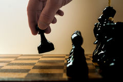 Chess player makes a move the black pawn forward Royalty Free Stock Photo