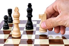 Chess player moving his piece. Player hand with a knight seen on chess board Stock Photo
