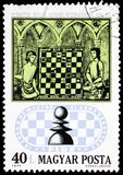 Chess Players from 15th Century Manuscript, 50th Anniversary of the International Chess Federation serie, circa 1974. MOSCOW, RUSSIA - MAY 25, 2019: Postage stock image