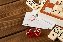 Chess, playing cards, dominoes on a wooden table. The concept of Board games stock images
